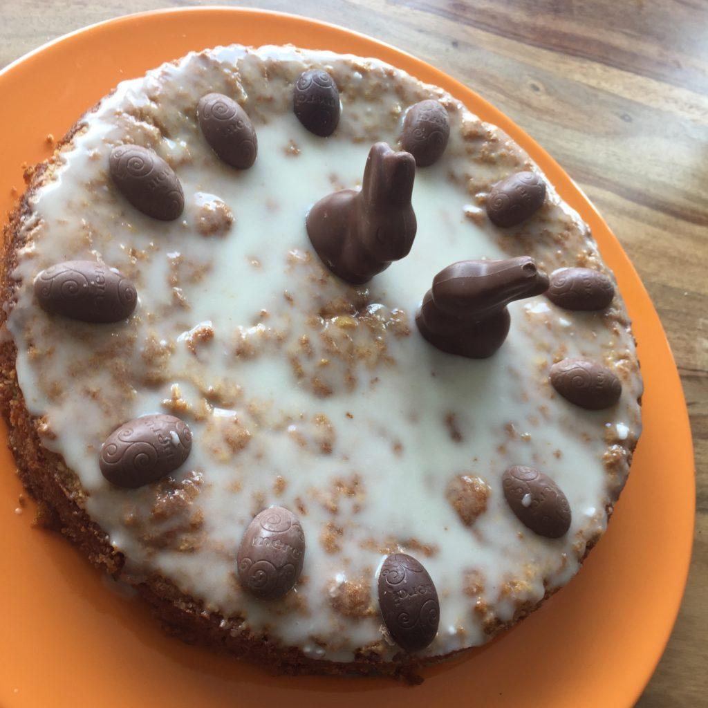 Möhrchenkuchen dekoriert mit zwei Schokoladenhasen und Schokoeiern
