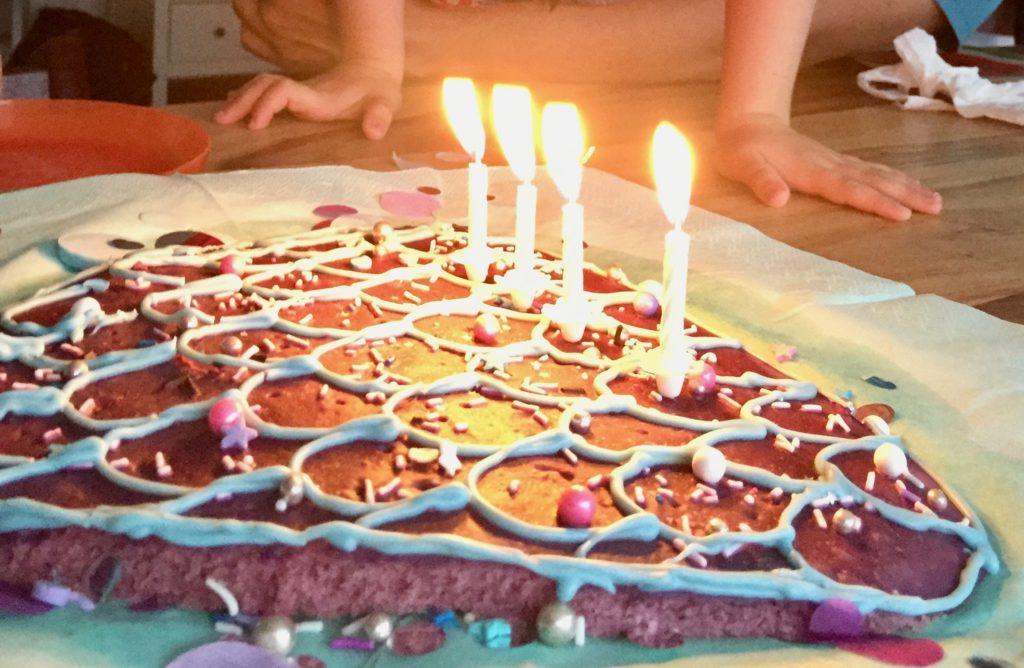 Ein aus einem lila Blechkuchen ausgeschnittene Meerjungfrauenflosse in hellblau, lila und Pink mit Zuckerperlen, Smarties und Glasur dekoriert auf einem hellblauen Untergrund mit lila, silber, blauen Konfettis dekoriert - der Mermaid-Cake