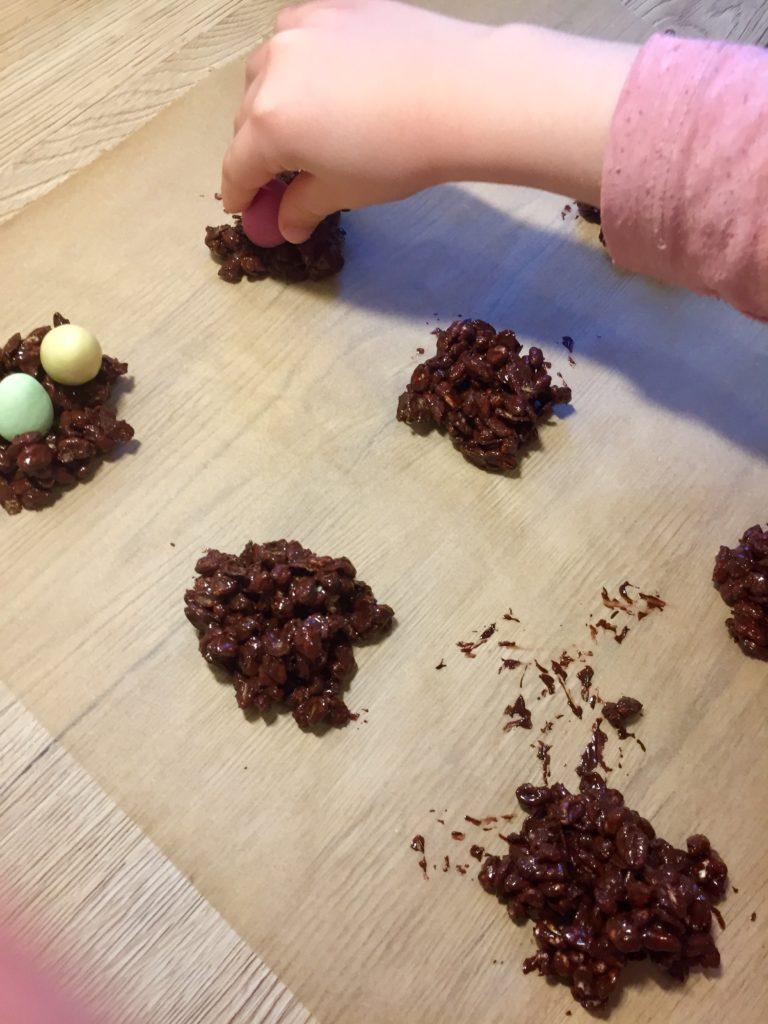 Kinder dekorieren die schokoladigen Osternester mit Schokoeiern, eine Aufgabe beim Backen mit Kindern, die schon die kleinen Kinder übernehmen können.