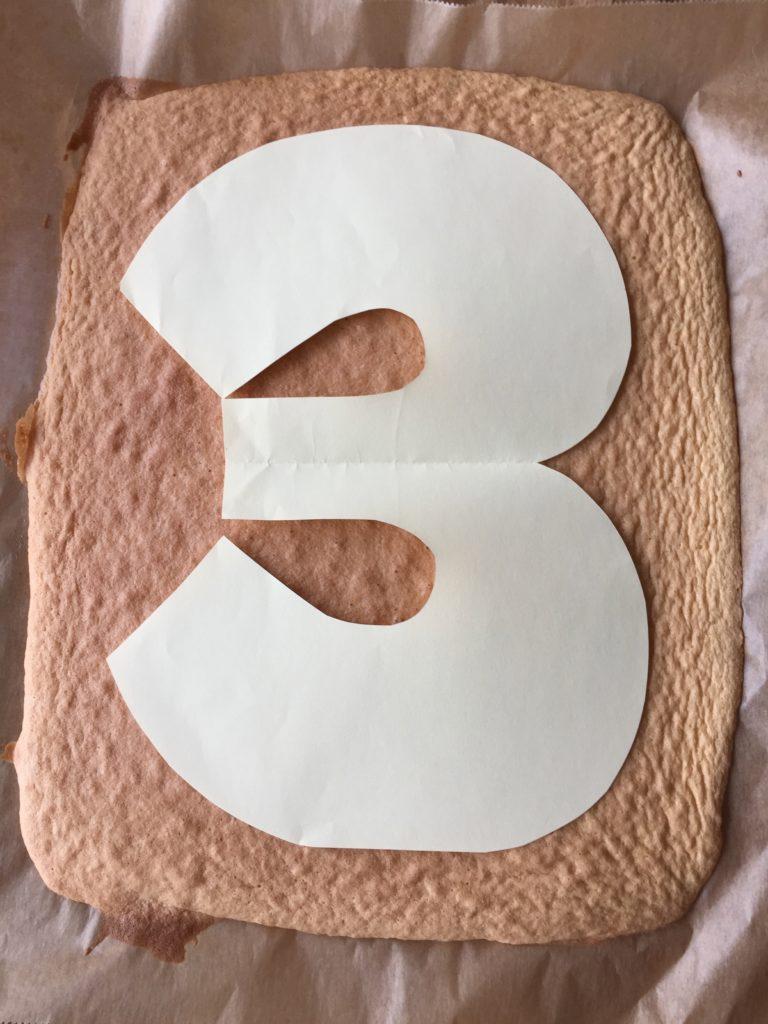 Die Zahl für den Number-Cake wird aus dem Biskuitboden geschnitten.