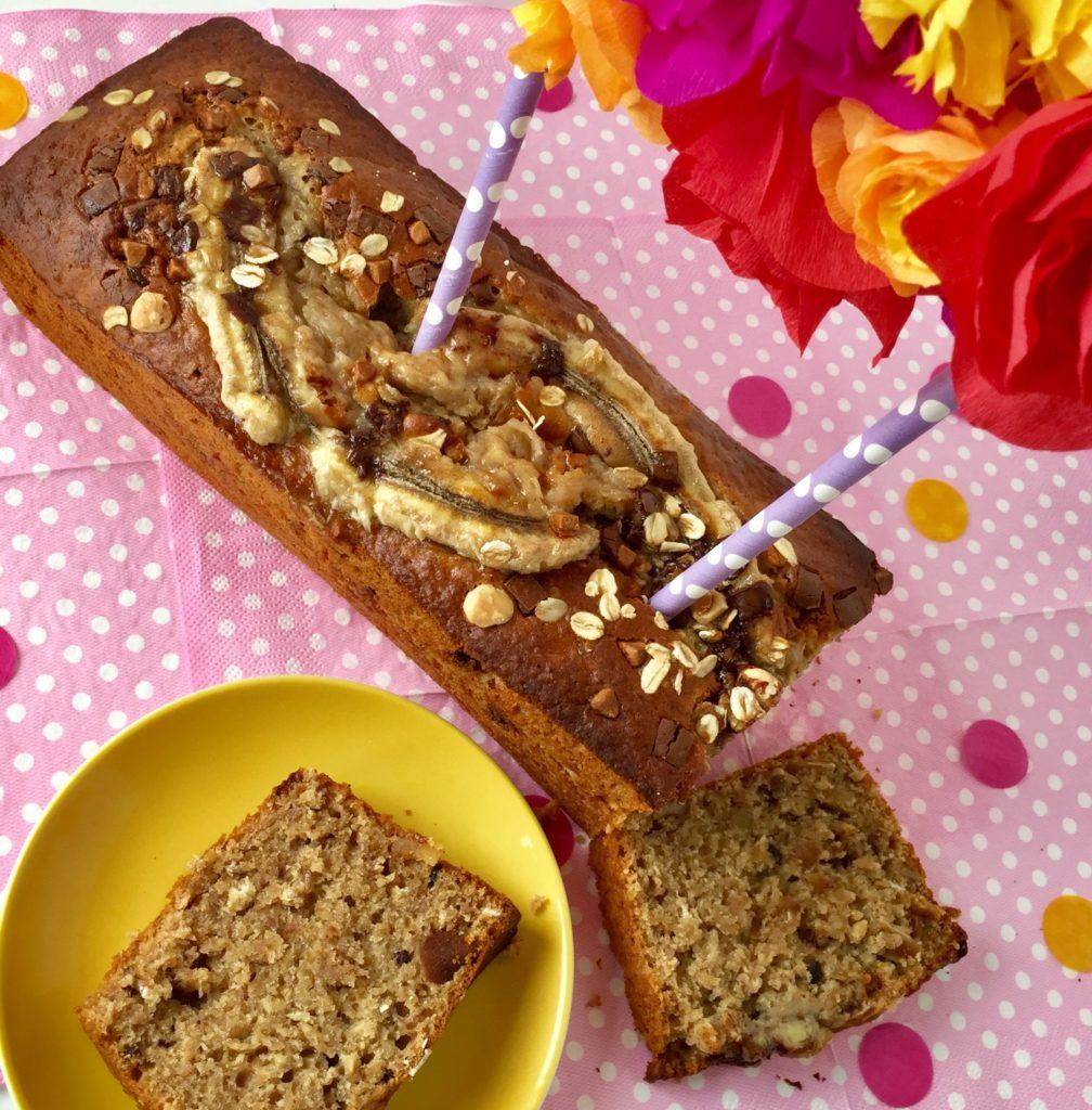 Gesundes Bananenbrot Deluxe mit Karamellcrunsh mit einer Blumengirlande und einem Stück des Kuchens auf einem gelben Teller.