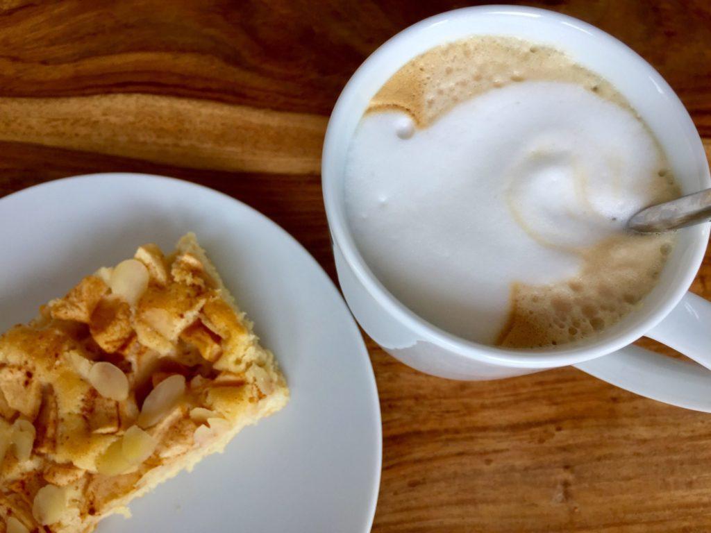 Ein Stück saftiger Apfelkuchen vom Blech mit einer leckeren Tasse Kaffee