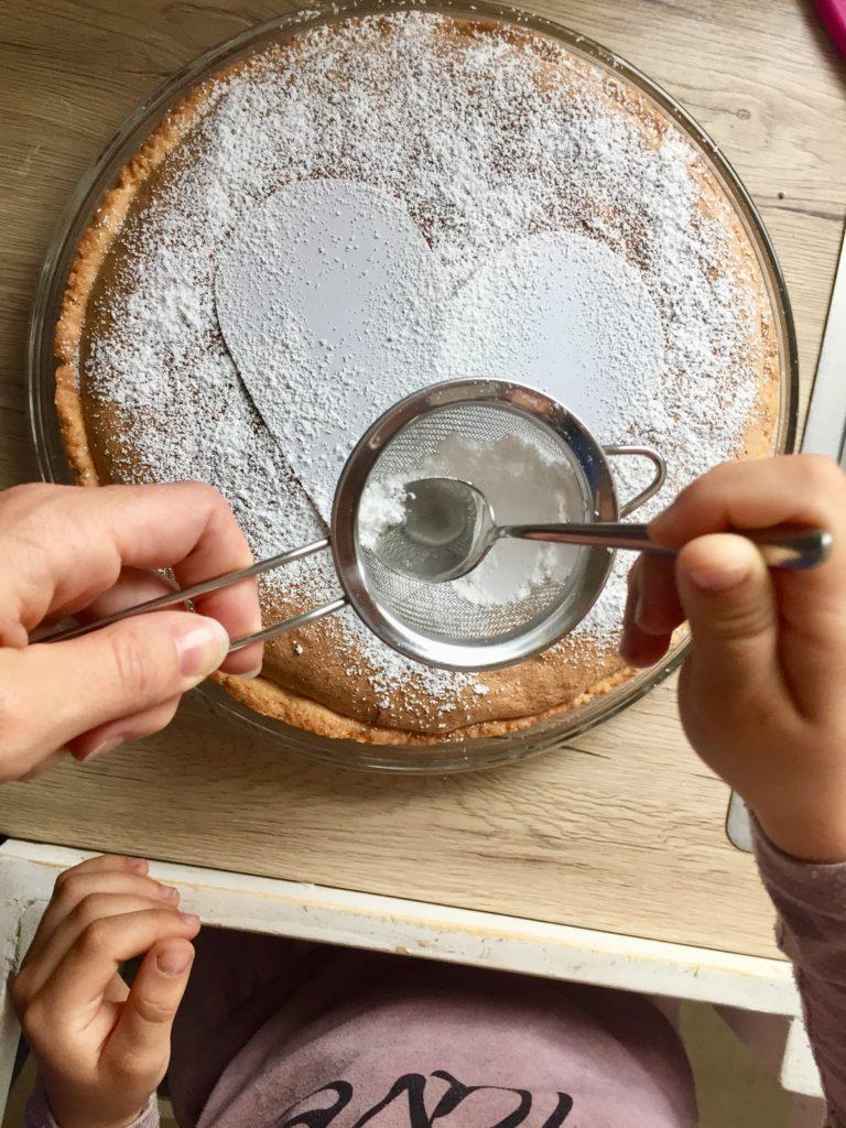 Der spanische Mandelkuchen wird mit einer Schablone und Puderzucker für dem Vatertag dekoriert