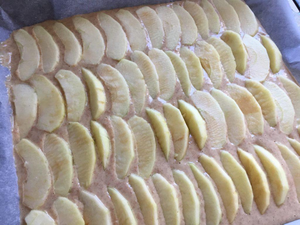 Die Apfelspalten werden auf den ungebackenen Kuchen gelegt.