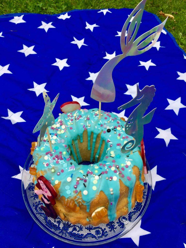 Der Geburtstagskuchen für die Meerjungfrauen Party mit hübschen Unter-Wasser-Caketoppern auf der Picknickdecke