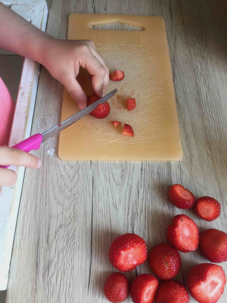 Das Backen mit Kindern gibt ihnen Selbstvertrauen und macht Spass, lass Kind die Erdbeeren schneiden.