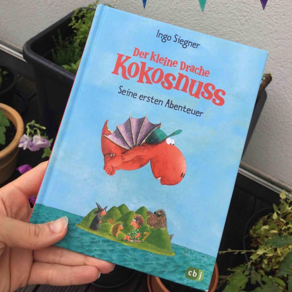 """Für die Interpretation der Kinderbücher heisst das Thema im Juli """"Der kleine Drache Kokosnuss - Alles um Drachen, Dinos und die Kokosnuss"""""""