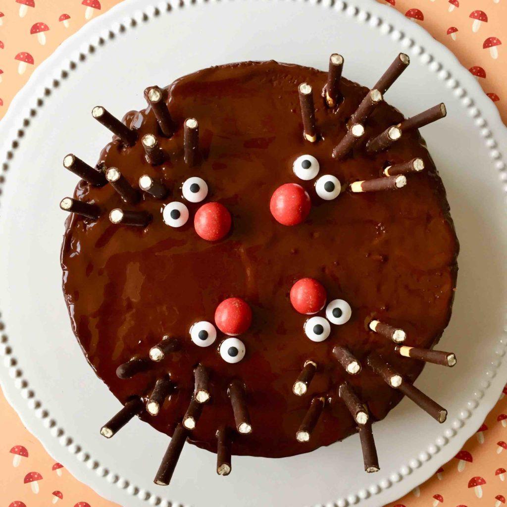 Ein Schoko-Nuss-Kuchen mit vier kleinen Igeln als Igelkuchen  gestaltet aus einer roten Nase aus M und Ms, Zuckeraugen und Micadostäbchen als Stacheln auf einer weißen Kuchenplatte auf einem Papieruntergrund mit aufgedruckten Pilzen.