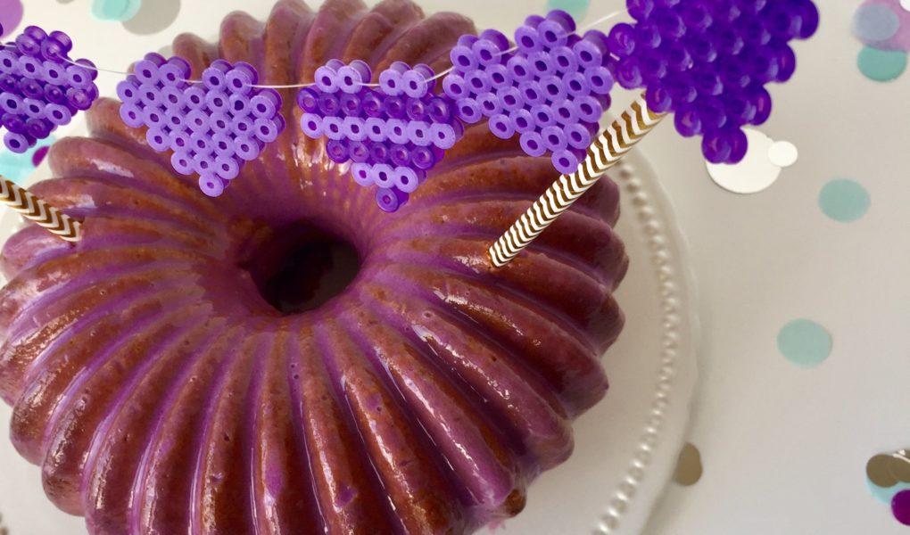 Ein Vanille-Gugelhupf mit lila Mirror Glaze und einem Caketopper aus Bügelperlen
