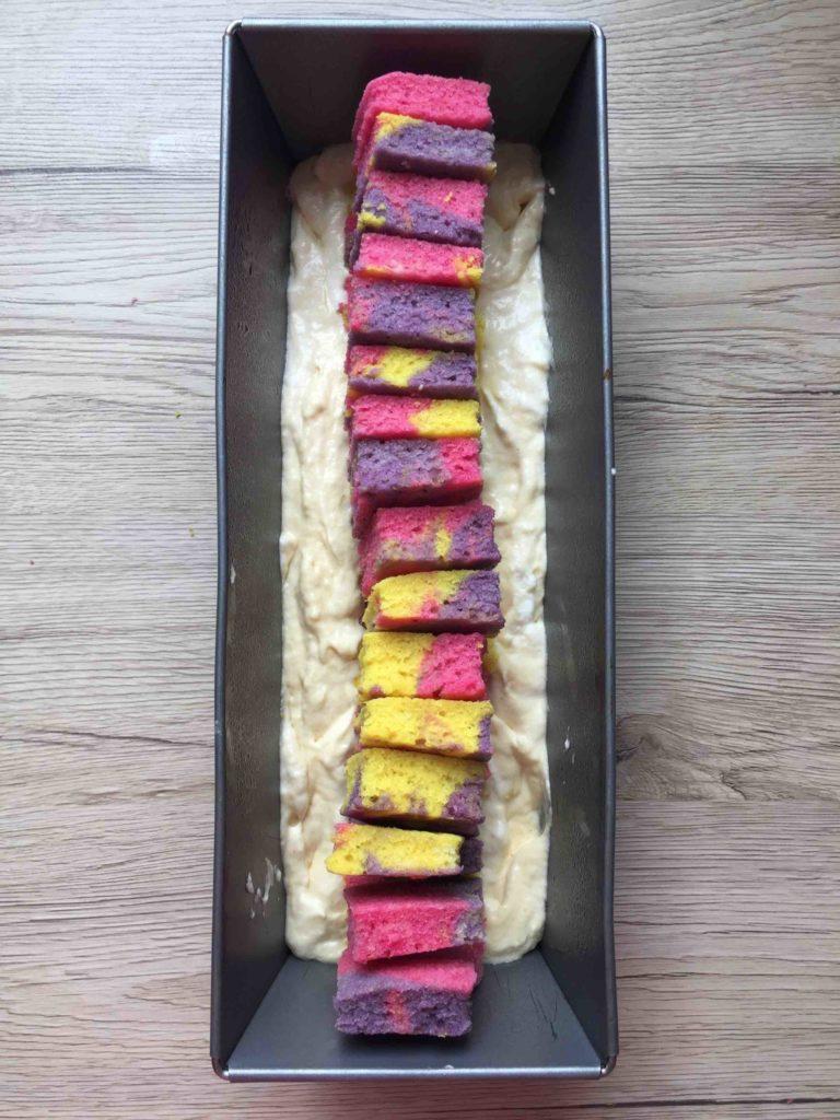 Die gebackenen, bunten Zahlen werden aufrecht in die zu ein Drittel mit Teig gefüllte Kastenform gestellt. So entsteht die Zahl im Kuchen.