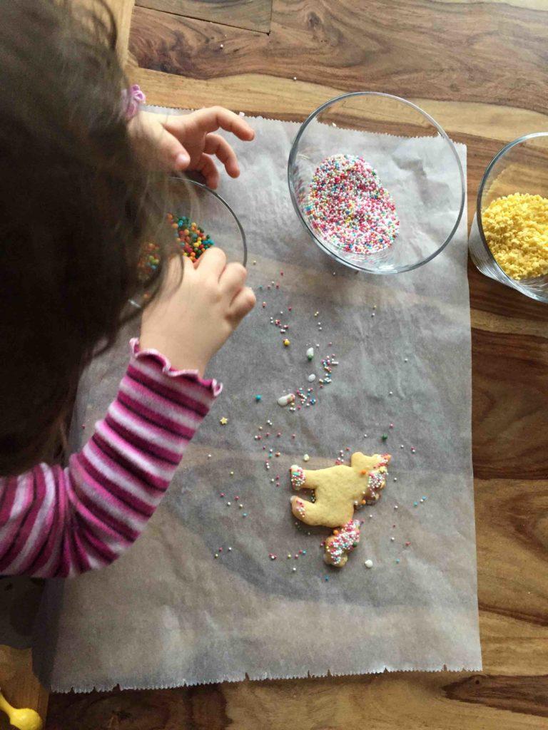 Ein Kind bestreuselt die selbstgebackenen Plätzchen mit Zuckerstreuseln. Wie das Dekorieren und Plätzchen backen mit Kindern in der Weihnachtszeit zum Erfolg wird, zeigen dir diese Backtipps.