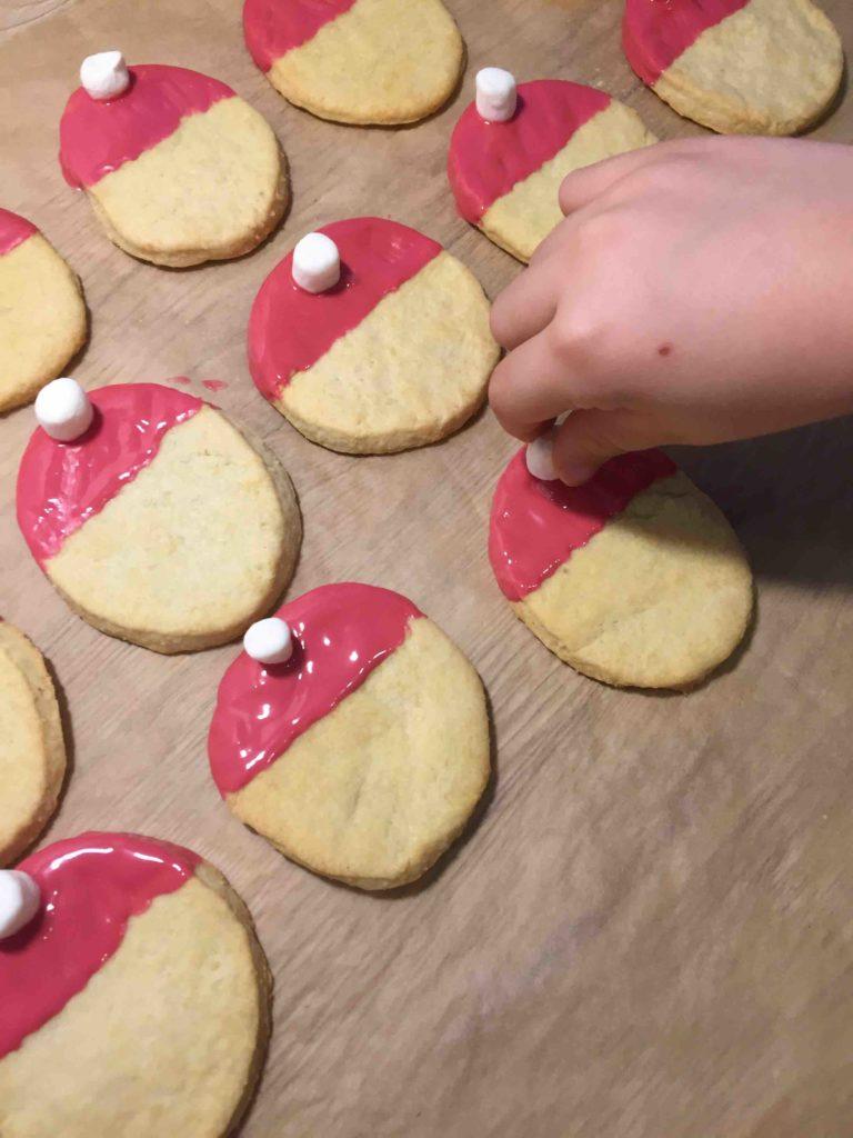 Hochkonzentriert werden die Santa Claus Cookies von Kinderhänden dekoriert.