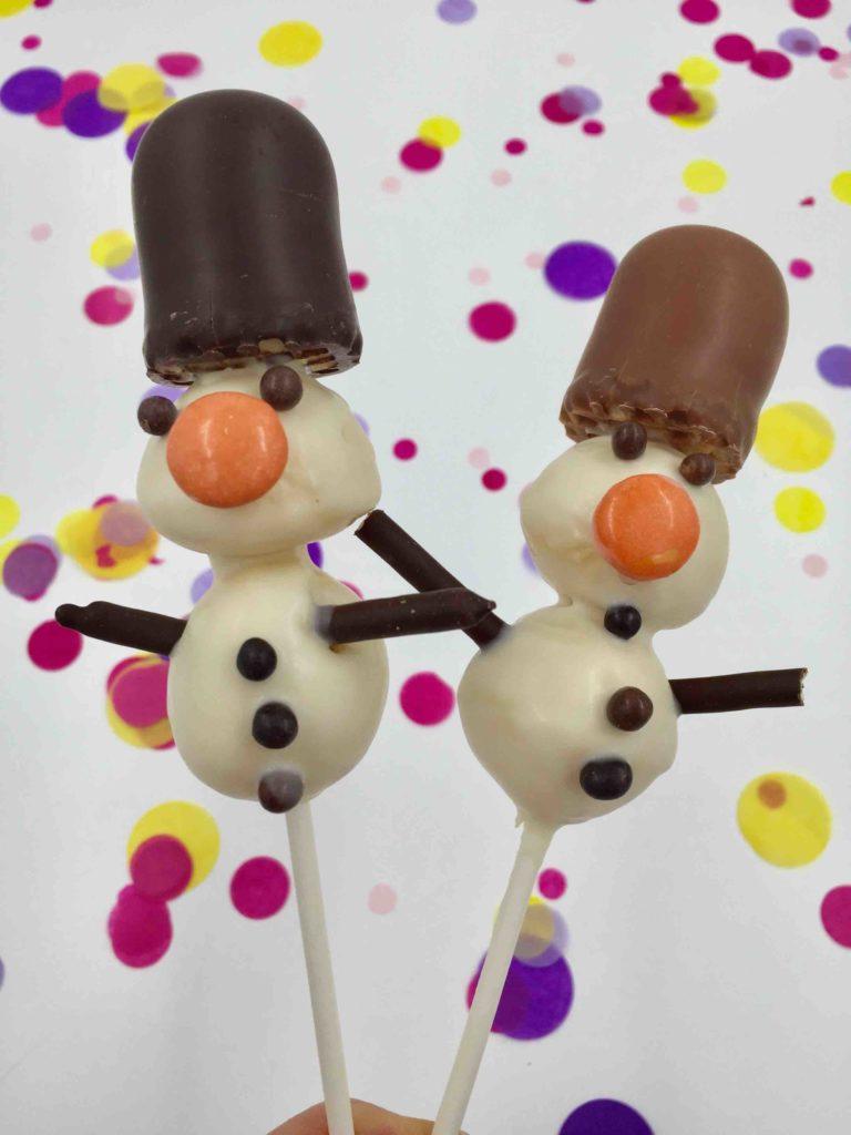 Zwei Cakepops mit einem Schokokuss als Hut ergeben Schneemann-Cakepops beim Backen mit Kindern