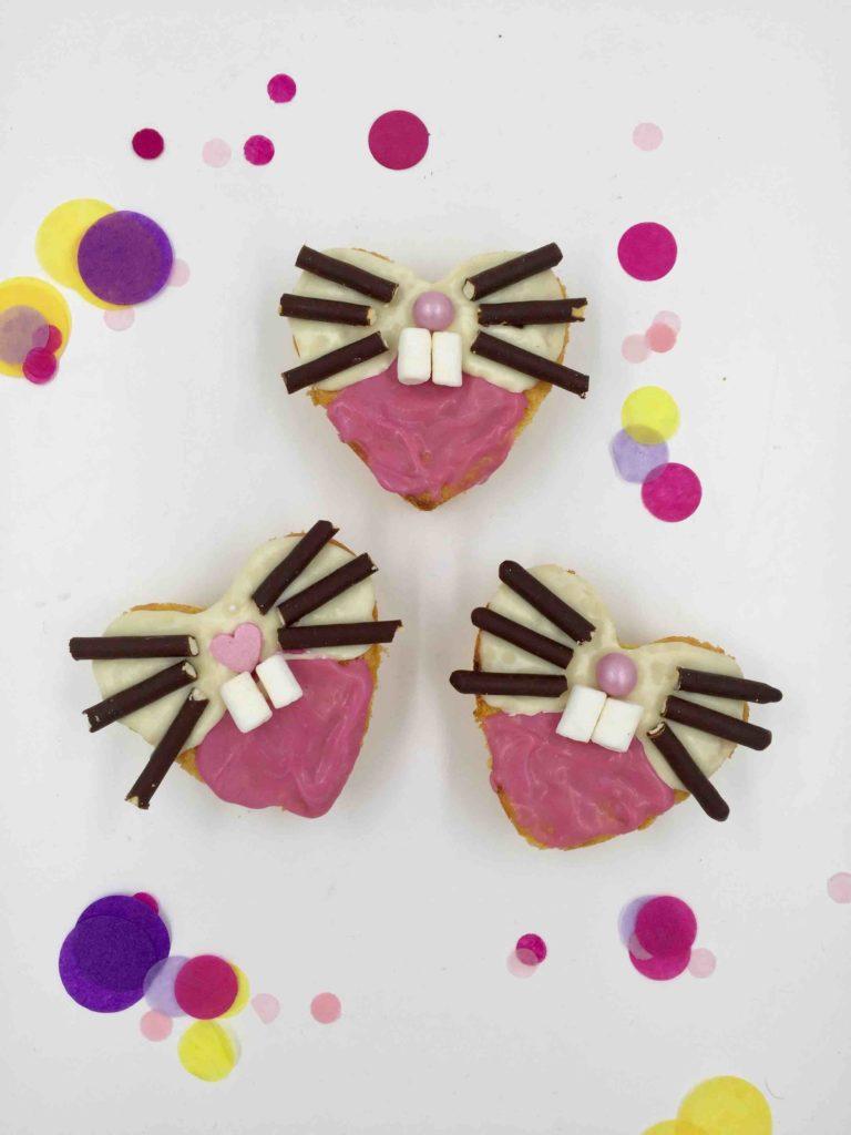 Der in einer Herzform gebackene Möhrenkuchen wird als Hase dekoriert und auf das Cakeboard für Ostern gesetzt.