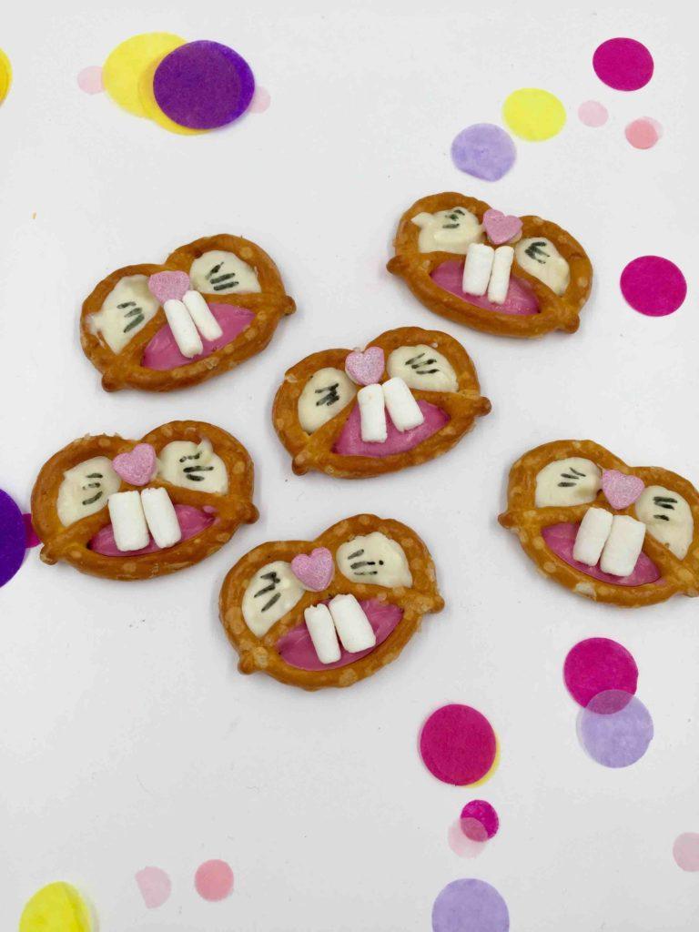 Die kleinen Brezel werden mithilfe von Schokolade zu kleinen Osterhasen für das Cakeboard für Ostern.