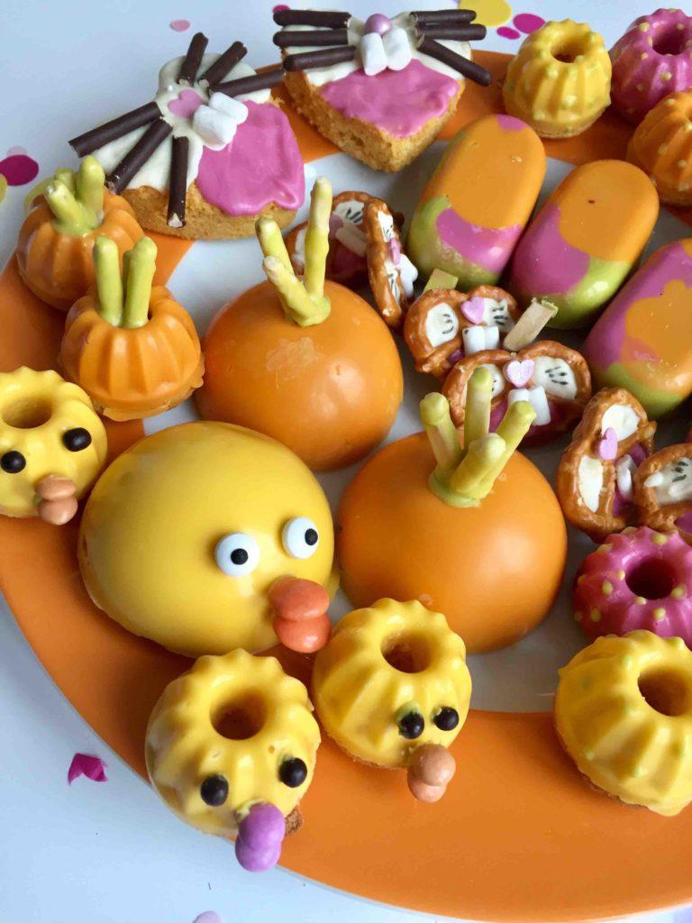 Ein buntes Cakeboard für Ostern mit Möhrenkuchen in verschiedenen Formen gebacken- Hasen, Küken, Möhre