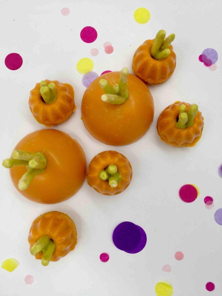 Die aus Mini-Gugelhupfen geformten Möhren werden auf das Cakeboard für Ostern gesetzt.