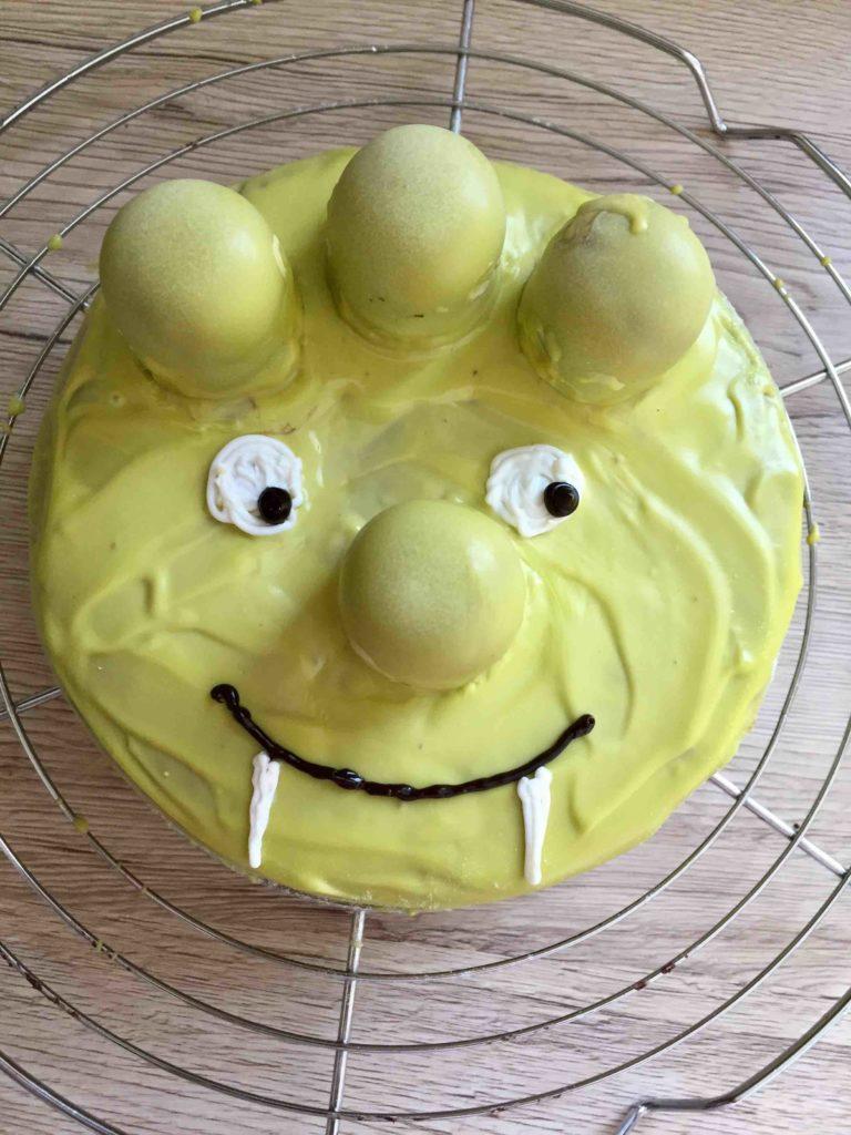 Der mit grünen Cake Melts dekorierte Zebrakuchen wird zum Olchi
