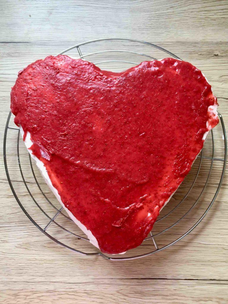 Die Erdbeer-Quark-Torte wird mit einem fruchtigen Erdbeer-Topping bestrichen.