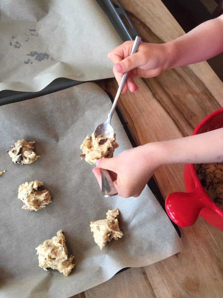 Die Kinder verteilen den Teig der Chocolate Chip Cookies allen mit zwei Löffeln auf dem Backblech.