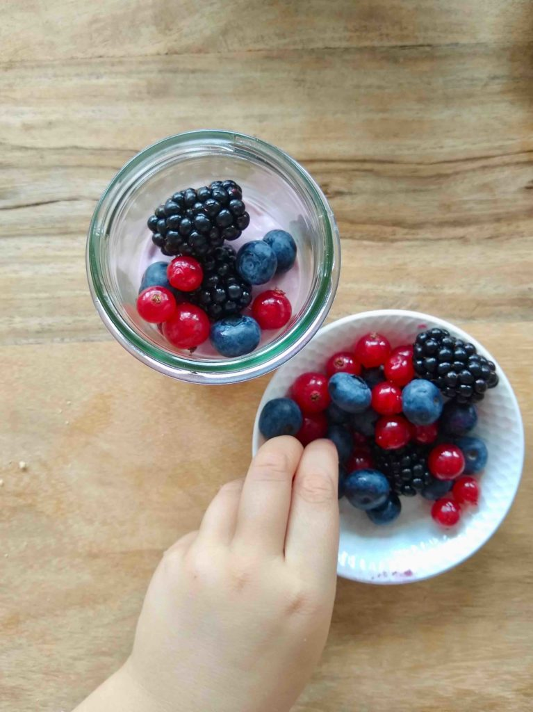 Fruchtige No-Bake-Cakes im Glas mit verschiedenen Beeren - eine schnelle Picknickidee zum Selbermachen mit Kindern